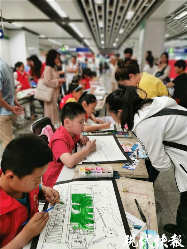 六一儿童节,30名小朋友在南京地铁站里玩嗨了 绘画结束后,地保办执法队员和热心乘客为自己喜爱的绘画作品贴上地铁执法小合的卡通人物标签。生动鲜明的小合形象与天真朴实的儿童作品浑然一体,构成了别样的六一作品。在精心的评比后,共评出一等奖一名,二等奖三名,三等奖六名。小朋友们拿着自己的作品与执法队员们合影留念,庆祝自己的节日。