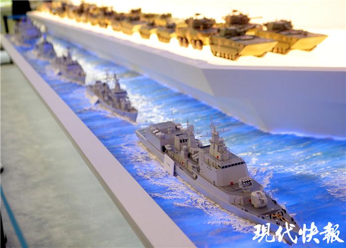 亲眼看到如此多最先进最前沿的武器装备模型,观众们也为之着迷。久久停留在模型展台边,将每个模型看个遍。 在一层打头阵的是两艘航空母舰,分别是辽宁号航空母舰和我国第二艘航空母舰模型。紧随其后的是,不同系列、型号的核潜艇、驱逐舰、护卫舰、坦克、两栖突击车等武器装备模型。不经意间,抬起头还能收获惊喜,一架架不同型号的飞机模型,正列队悬挂在展厅上方。